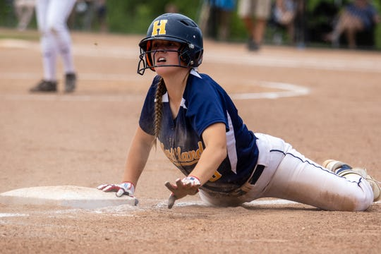 Hartland's Brooke Cowan dives back into third base in a 7-6 victory over South Lyon East in the regional championship game on Saturday, June 8, 2019.