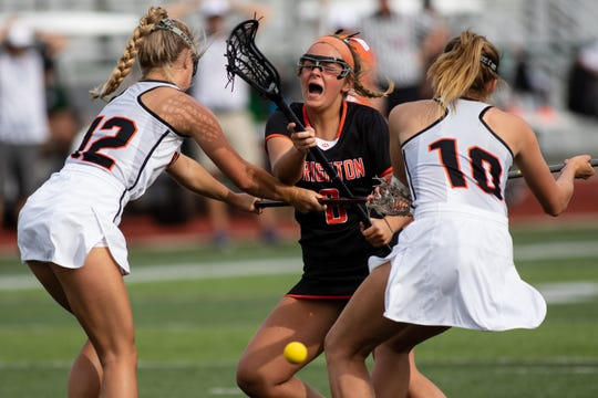 Brighton's India Lange is thwarted by Rockford defenders Shae Strehl (12) and Bailey Banfield (10) during the state Division 1 lacrosse championship game at Novi on Saturday, June 8, 2019.
