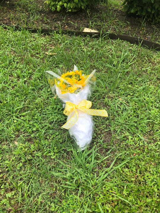 Flowers were left in the grass beside the parking lot where Glenn Cofield was shot and killed Friday.
