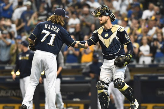 Josh Hader is congratulated by catcher Yasmani Grandal after he closed out the Brewers' 5-2 win over the Pirates with his 16th save of the season Sunday.