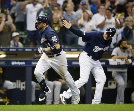 Mike Moustakas makes his way past Brewers third base coach Ed Sedar on his way to the plate after belting a two-run home run against the Pirates in the eighth inning.