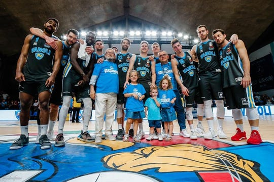 Travis Diener (center) and his three children with the Vanoli Cremona basketball team.
