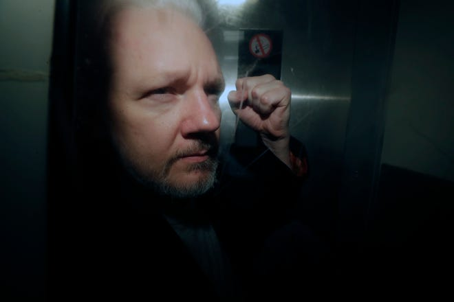 FILE - In this May 1, 2019, file photo, WikiLeaks founder Julian Assange puts his fist up as he is taken from court in London. The Justice Department has charged Assange with receiving and publishing classified information. The charges are contained in a new, 18-count indictment announced May 23, 2019. (AP Photo/Matt Dunham, File)
