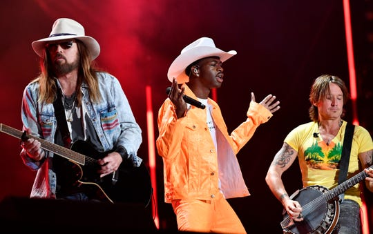 Lil Nas X performs with Billy Ray Cyrus and Keith Urban during the CMA Music Festival on June 8, 2019, at Nissan Stadium in Nashville.