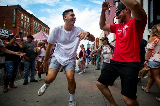 Cody Martin, left, dances with his brother Kyle Martin, in the middle of the sidewalk to the music coming from the open windows of Kid Rock's Big Honky Tonk Rock 'n Roll Steakhouse on Lower Broadway during the CMA Fest in Nashville on Saturday, June 8, 2019. Cody Martin was celebrating his bachelor party weekend.