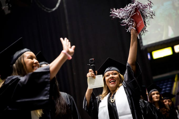 Graduates wave to their friends and families as they process in during the commencement ceremony for Hodges University at Hertz Arena in Estero on Sunday, June 9, 2019. 480 students graduated receiving Master's, Bachelor's, and Associate's Degrees as well as professional certificates.