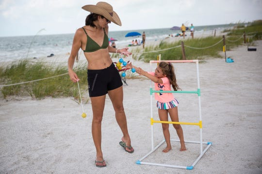 Jill Leonetti, left, and Mia Leonetti, 4, right, play ladder ball during a World Oceans Day celebration at Lovers Key State Park on Sunday, June 9, 2019.