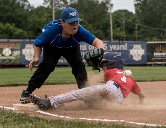 Licking Valley Lions' Noah Curry slides safely into third base Saturday during a Varsity Division game against Mound City's Park National Bank. The Lions won to advance to the Licking County Shrine Tournament quarterfinals at Mound City.
