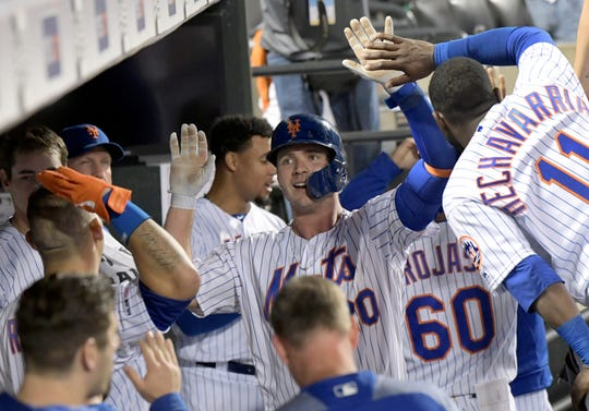 New York Mets' Pete Alonso, center, celebrates with teammates after hitting a home run during the seventh inning of a baseball game against the Colorado Rockies, Saturday, June 8, 2019, in New York.