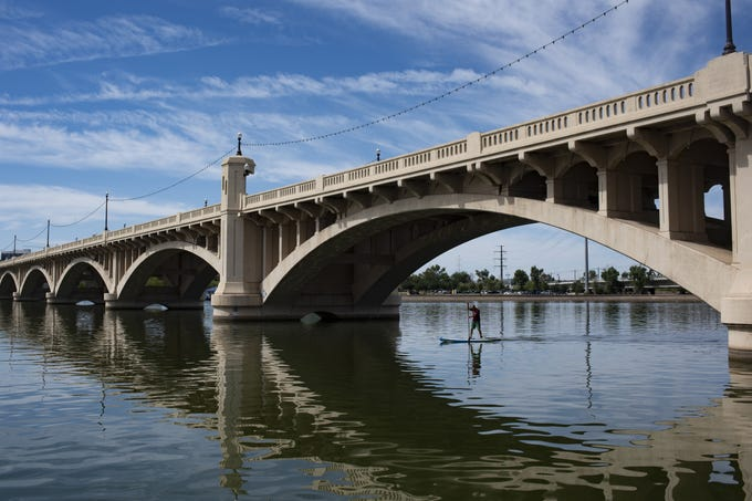 A man paddle boards across Tempe Town Lake on a warm Sunday morning in Tempe on June 9, 2019.