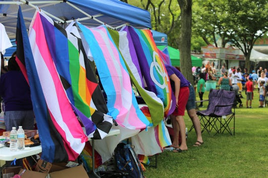 A row of LGBTQ+ flags are displayed as part of Dutchess County Pride Center's booth at the City of Poughkeepsie's first pride festival in Waryas Park on Sunday, June 9, 2019.