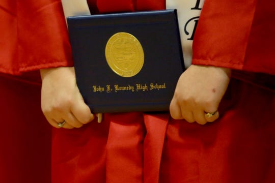 A graduate holds their diploma during the Kennedy High School commencement at Kennedy High School in Mt. Angel on June 8, 2019.