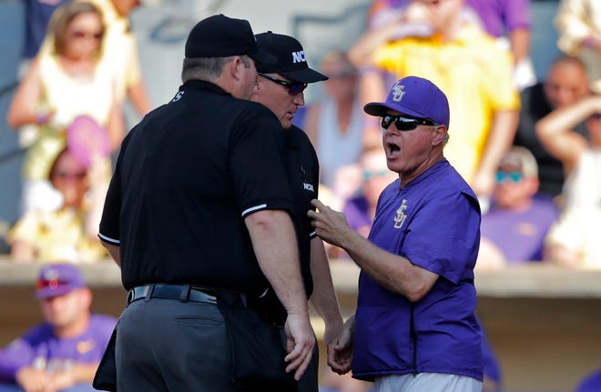 LSU head coach Paul Mainieri, right, challenges the umpire after a called out at the plate by Florida State runner Robby Martin was overturned due to a fielding error by LSU catcher Saul Garza in the second inning of Game 2 of the NCAA college baseball super regional tournament in Baton Rouge, La., Sunday, June 9, 2019. (AP Photo/Gerald Herbert)