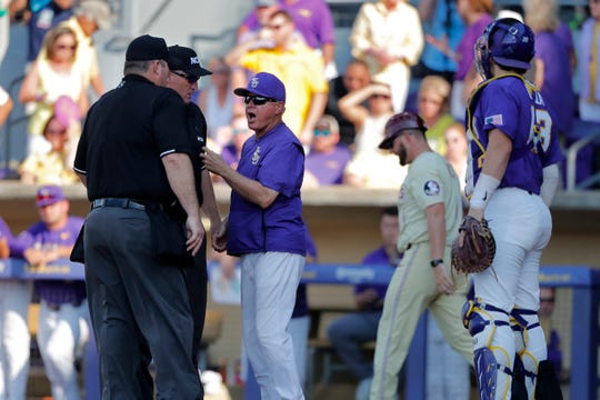 LSU head coach Paul Mainieri challenges the umpire after a called out at the plate by Florida State runner Robby Martin was overturned due to a fielding error by LSU catcher Saul Garza in the second inning of Game 2 of the NCAA college baseball super regional tournament in Baton Rouge, La., Sunday, June 9, 2019. (AP Photo/Gerald Herbert)