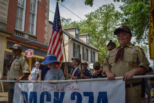 Members of the Boy Scouts of America Pack 27 carry a banner during the Separation Day Parade. The festival is a fundraising opportunity for many nonprofit groups.
