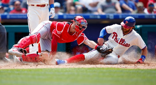Philadelphia Phillies' Bryce Harper, right, is tagged out by Cincinnati Reds catcher Curt Casali after trying to steal home during the fifth inning of a baseball game, Sunday, June 9, in Philadelphia.