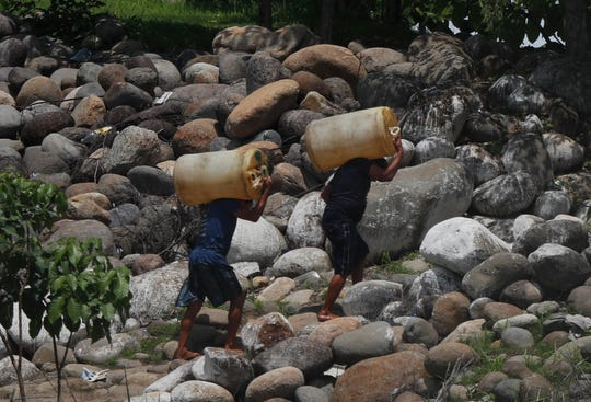 Men carry containers of black-market gasoline, recently brought illegally across the Suchiate River on rafts, near Ciudad Hidalgo, Mexico. Some migrants pay raft operators in order to avoid swimming or going through the official border crossing.