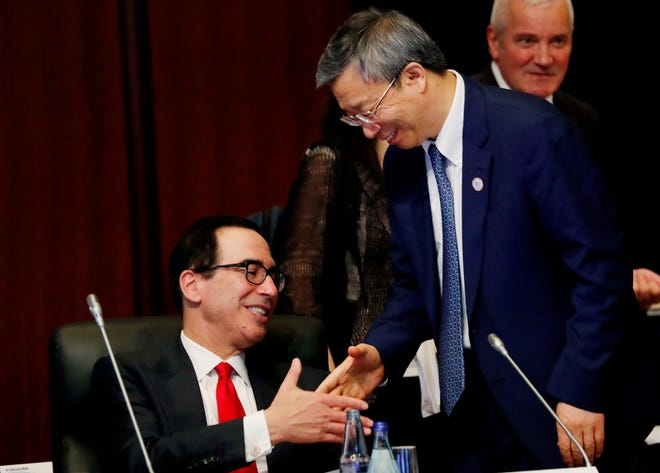China's Central Bank Governor Yi Gang shakes hands with U.S. Treasury Secretary Steve Mnuchin, left, during the G20 Finance Ministers and Central Bank Governors Meeting Saturday, June 8, 2019, In Fukuoka, Japan.
