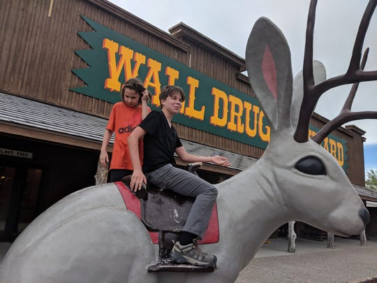 Erysse and Iden Elliott on a giant jackalope at Wall Drug Store in South Dakota.