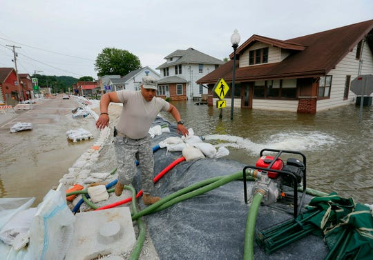 Illinois National Guard Sgt. Joey White climbs the temporary flood wall built on Main Street in Grafton, Ill., Saturday, June 8, 2019.