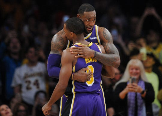 Lakers forward LeBron James (23) is greeted by guard Rajon Rondo (9) during a game this season.
