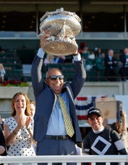 Sir Winston trainer Mark Casse lifts up the Belmont Trophy. He also won the Preakness with War of Will.