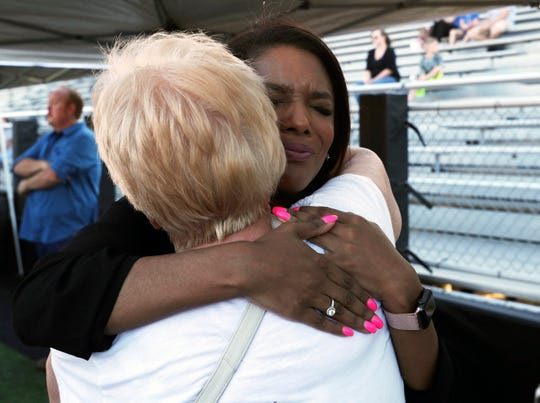 Kristi Wyatt hugs a friend after speaking at a gathering for Kemah Police Chief Chris Reed at Veterans Memorial Stadium in League City, Texas, on June 8, 2019.