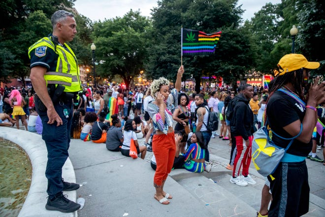 Police keep watch at Dupont Circle at the conclusion of the Capitol Pride Parade in Washington, Saturday, June 8, 2019. Officials in Washington say several people were injured after a panic at the LGBTQ pride parade sent people running through the streets of the nation's capital.