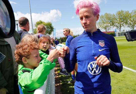 United States forward Megan Rapinoe bumps fists with a fan during training for the FIFA Women's World Cup.