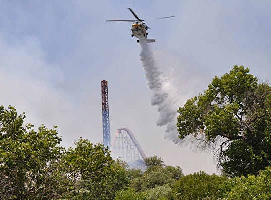 Los Angeles County Fire helicopter drops water on brush fire burning close to Six Flags Magic Mountain and Hurricane Harbor amusement park in Santa Clarita, Calif., Sunday, June 9, 2019.