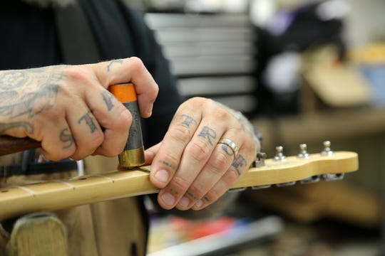 Kyle Roggendorf, owner of Raritan Bay Guitar Repair, a long-standing, full service fretted and stringed instrument repair facility, works on a guitar in his business location in Freehold Twp., NJ Monday June 10, 2019.