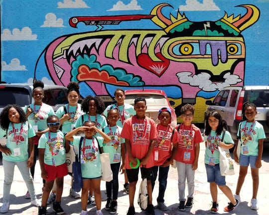 DeSoto students in their Genius T-shirts photographed by a downtown Abilene mural.