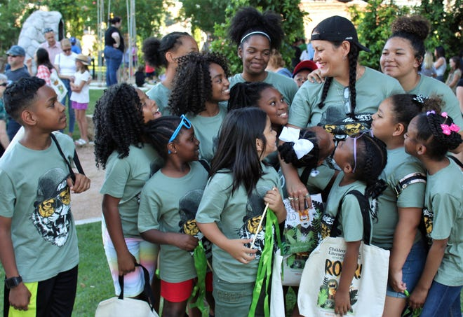 "Teacher Megan Mitchell (top, second from right) is surrounded by students from the DeSoto ISD whom she brought to last weekend's Children's Art & Literacy Festival. They wore matching T-shirts with their version of a cool tiger on the front and ""Mr. Tiger Goes Wild"" on the back for the unveiling of Peter Brown's Mr. Tiger sculpture in Adamson-Spalding Storybook Garden. They wear a author-illustrator T-shirt Thursday now, the CALF T-shirt Fridays and a Genius shirt for Smart Scholars Saturdays."