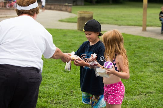 In this 2015 photo, Marieanne Boyer, site supervisor, hands out lunches to Damien Coleman, center, and Destiny Crumb at Piper Park as part of the Meet Up and Eat Up. program.