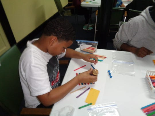 Elijah Johnson works on a craft at Crosspoint Community Church. He participates in Friday Friends, an afterschool faith-based program held at the church on Fridays during the school year.