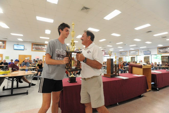 Wyatt Lehman receives the Owen High School Male Athlete of the Year Award from athletic director Anthony Lee.