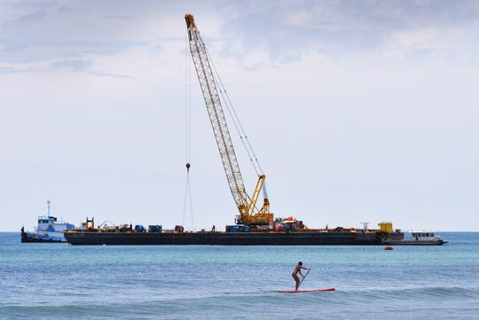 Gabrielle Berube paddles a stand-up paddleboard past the barge in the background just south of the DoubleTree Hotel in Indialantic that was installing reefs. Shoreline Foundations Inc. began placing 8-by-12-foot rectangular reef segments about a quarter-mile offshore of Indialantic this month.They are finishing the last 15 percent of a $10.6 million artificial reef that must be installed before dredges can pump sand on Satellite Beach and Indian Harbour Beach, beginning late this year. That $15 million project is expected to bring 275,000 cubic yards of new sand to those two beaches.