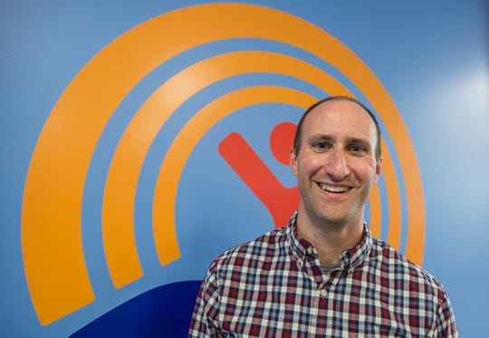 Jesse Bridges, CEO of the United Way of Northwest Vermont, stands in front of the organization's symbol. The organization is a recipient of A Community Thrives Local Grant which they will use to expand their Working Bridges program.