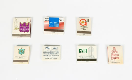 A collection of matchbooks from assorted Corpus Christi businesses. They include (top row, left to right), The Spanish Main, the Rusted Rail (celebrating the Bicentennial), and Guaranty National Bank; (bottom row, left to right) The Robert Driscoll Hotel, Sand and Sea Resort, Guaranty National Bank and Panjo's Pizza Parlor.