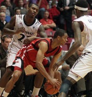 Jacksonville State Gamecocks guard Dion Waiters (1) is surrounded by Cincinnati Bearcats players Sean Kilpatrick and Octavius Ellis in 2011.