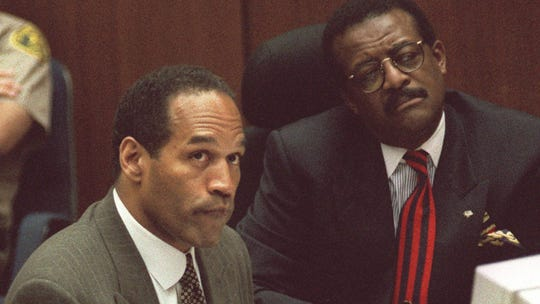 Text: O.J. Simpson looks at an overhead screen as biochemist Robin Cotton explains genetic markers on DNA film during the Simpson double-murder trial in Los Angeles Wednesday morning, May 10, 1995. Cotton for the first time linked Simpson to the murders of his ex-wife and her friend, telling jurors DNA in a blood drop found near the bodies matched Simpson's. At right is Simpson's attorney, Johnnie Cochran Jr.(AP Photo/Vince Bucci, Pool)