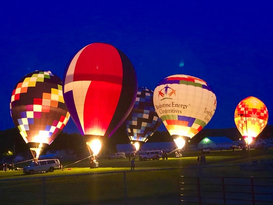 Night Glow, a popular attraction during the Coshocton Hot Air Balloon Festival, is where balloonists fire their propane flames in time with music to form patterns for viewing by the audience.