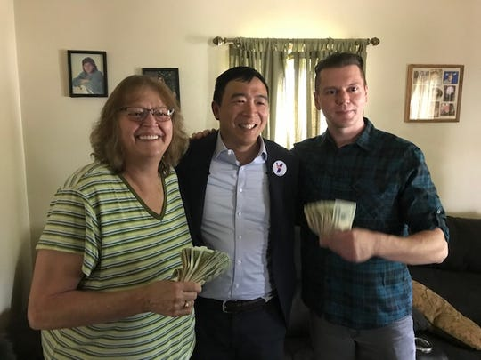 Presidential candidate Andrew Yang, center, named Kyle Christensen of Iowa falls, left, to receive $1,000 a month for 12 months from Yang. Kyle's mother, Pam Christensen is also pictured with them.