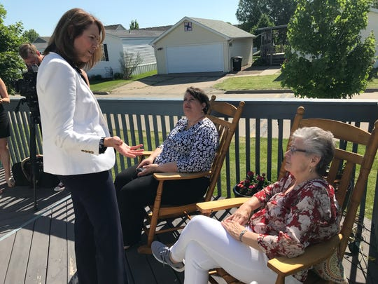 U.S. Rep. Cindy Axne, left, speaks with Lois Garwood, right, and Chris Crone during a visit to Garwood's home on Monday.