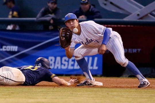 Michigan's Jimmy Kerr, left, dives into first base under the tag attempt by UCLA's Michael Toglia during the fifth inning of an NCAA college baseball tournament super regional game in Los Angeles, Sunday, June 9, 2019.