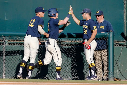 Michigan's Jack Blomgren, second from left, is greeted by teammates after hitting a a single during the second inning of an NCAA college baseball tournament super regional game in Los Angeles, Sunday, June 9, 2019.