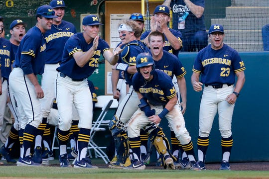 Michigan's Jack Blomgren, front, celebrates with teammates after he scoring against UCLA during the fifth inning of an NCAA college baseball tournament super regional game in Los Angeles, Sunday, June 9, 2019.