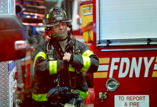 A New York City firefighter responds to the scene where a helicopter crash-landed on the roof of a midtown Manhattan skyscraper, Monday,  in New York.