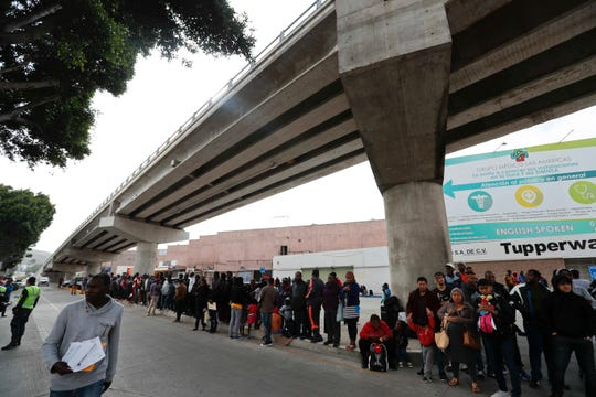 Migrants wait under a bridge to be attended to apply for asylum in the U.S., on the border in Tijuana, Mexico, Sunday, June 9, 2019.