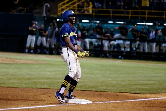 Michigan's Christan Bullock celebrates after hitting a triple against UCLA during the Super Regional.